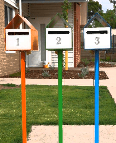 three letterboxes in front of green patch of grass